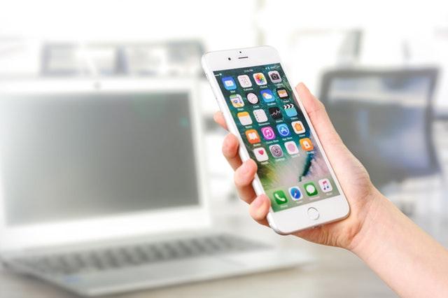 ruka držící zapnutý mobil v ruce s ikonama a v pozadí je notebook bílý