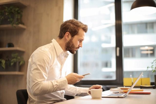 Mladší muž v bílé košili sedí v místnosti před notebookem a má v rukou mobil